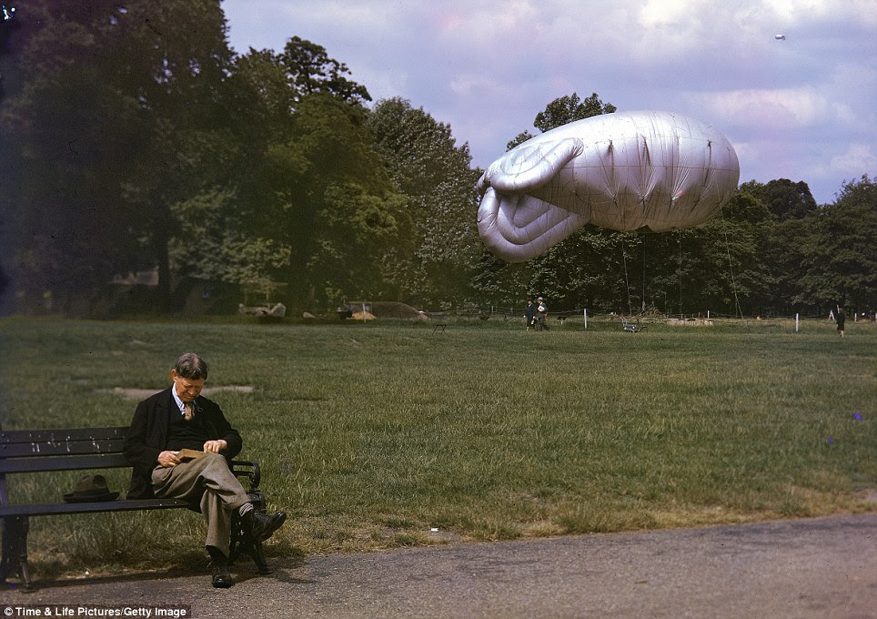 Stiff upper lip: A man reads a book while sitting on a park bench as a moored balloon floats in the background. A second one soars into the distance