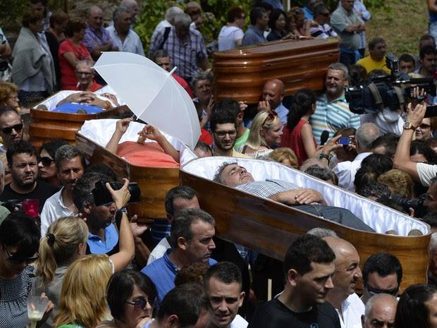Pessoas que passaram por situações em que escaparam da morte são carregadas em caixões por familiares na Procissão das Mortalhas, evento religioso que celebra Santa Marta agradecendo por não ter morrido, na vila de Santa Marta de Ribarteme, na Espanha (Foto: Miguel Riopa/AFP)