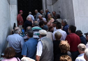 Elderly people, who usually get their pensions at the end of the month, wait outside a closed bank in the northern Greek port city of Thessaloniki, Monday, June 29, 2015. Greece's five-year financial crisis took its most dramatic turn yet, with the cabinet deciding that Greek banks would remain shut for six business days and restrictions would be imposed on cash machine withdrawals. (AP Photo/Giannis Papanikos)