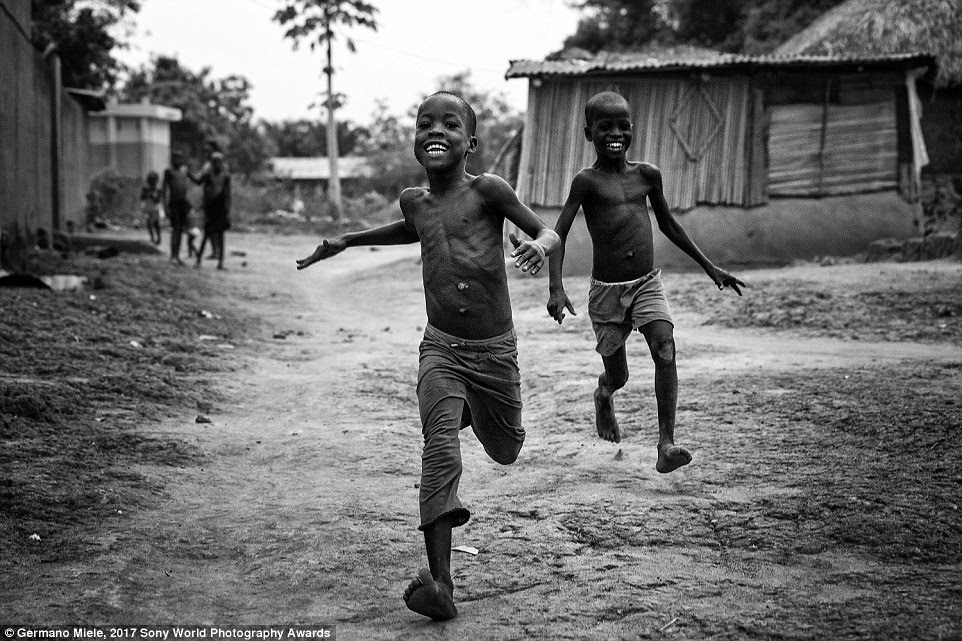 """Photographer Germano Miele writes of this image, which he took in the small village  in Benin: 'It's very common, when you leave the big cities to go discovering little villages, to be received like an old friend coming back home with amazing and unforgettable smiles and calling me """"Yovo"""" (white man in Fon, the local language). This is the pure Africa I really love'"""