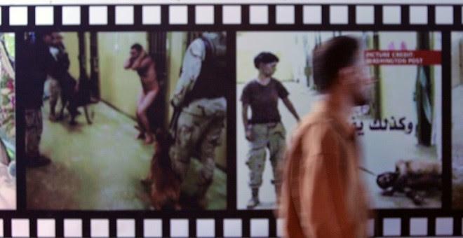 Un iraquí junto a unos paneles que muestran fotografías sacadas de la prisión de Abu Ghraib, gestionada por EEUU y donde los militares estadounidenses abusaban de los presos. - AFP