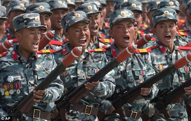 North Korean soldiers march with huge weapons as the country's foreign minister warns of war
