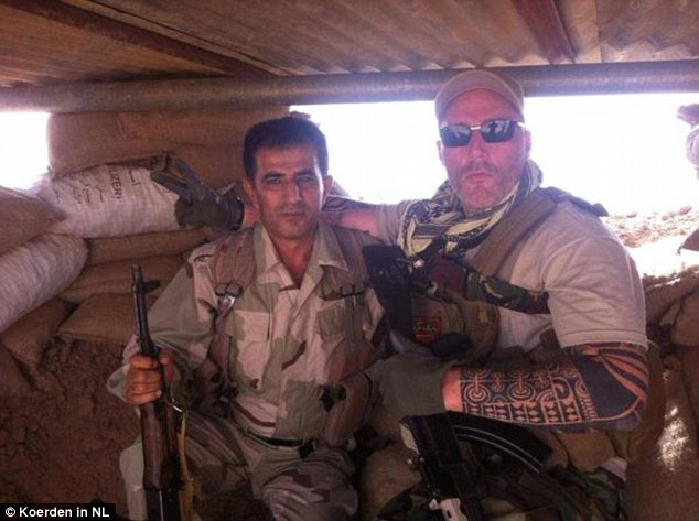 A biker from the No Surrender gang in the Netherlands, identified only as Ron (right) poses alongside a Kurdish soldier in Syria after going to fight against ISIS