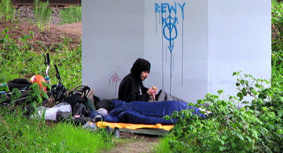 A homeless young man under a bridge
