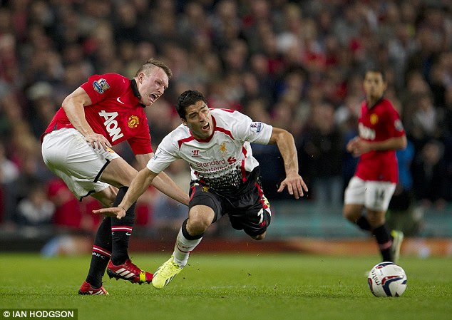 Ouch: United defender Phil Jones fouls Suarez with a crunching tackle