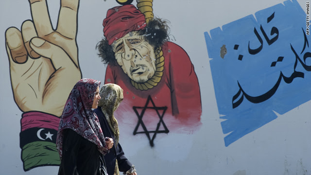 A woman looks over at an anti-Gadhafi mural as she walks past it with a friend in the rebel-held eastern port city of Benghazi on April 12, 2011.
