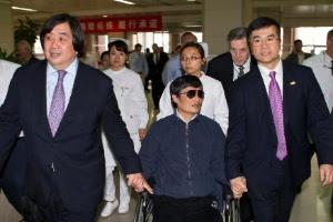 Em foto de 4 de maio, Chen (centro) sentado em uma cadeira de rodas é acompanhado do embaixador americano na China, Gary Locke, em hospital