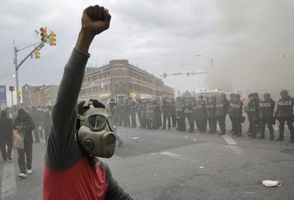 Rozando la medianoche, buena parte de Baltimore comenzaba ya a parecer una ciudad sitiada por la policía -más de 5.000 agentes han sido desplegados- que se hacía fuerte en las calles y avenidas principales. Foto: Boston Globe