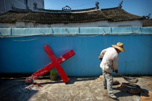浙江温州平阳的一位教徒试图重新竖起两天前被当局拆除的十字架(2015年7月29日)