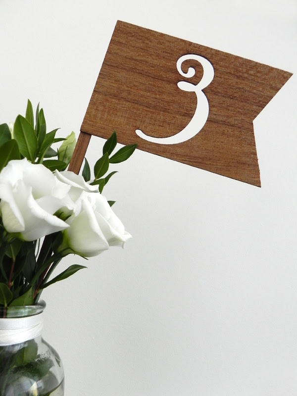 Lasercut wooden flags served as table numbers while laser engraved