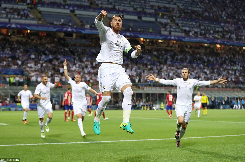 Ramos pumps his fists in delight after breaking the deadlock at the San Siro much to the delight of his Real Madrid team-mates
