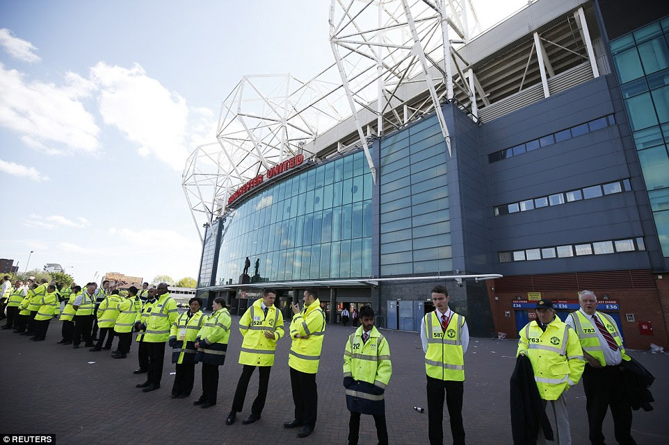 Stewards line up outside Old Trafford after the stadium was fully evacuated ahead of kick off following the discovery of a suspect package