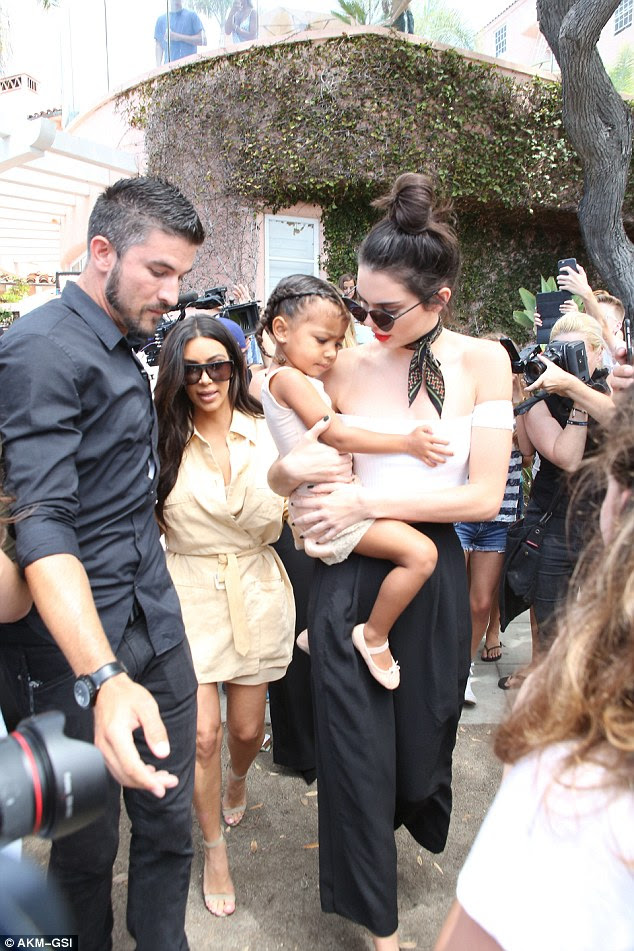 You're on camera: Kendall held on tightly to the tot, whose dad is Kanye West as photographers and cameras from their E! reality series surrounded them