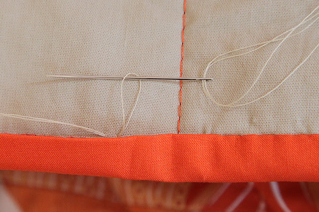 Hand sewing the binding down on the quilt