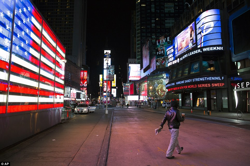Alone: A lone pedestrian walks through an empty Times Square early on Monday morning in New York as Hurricane Sandy continued on its path