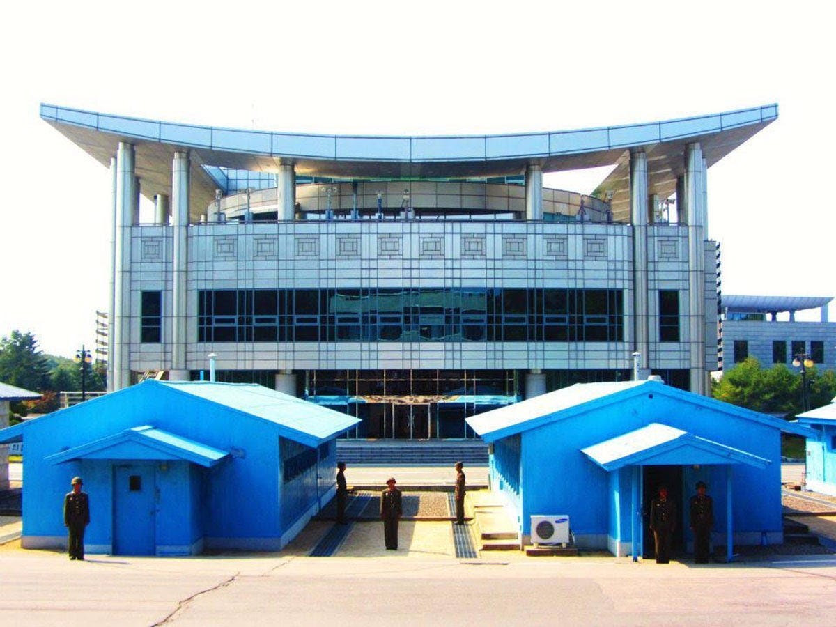 """The border between South Korea and North Korea starts at the concrete line between the blue huts pictured here. Former US President Bill Clinton once called the area, which is the most heavily militarized border in the world, """"the scariest place on Earth."""""""