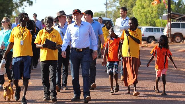 Australian PM Tony Abbott walks with indigenous Australians from the Yirrkala community t
