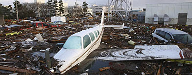 A plane and vehicles are submerged in debrls washed away by a devastating tsunami in Natori city, Miyagi Prefecture, northern Japan, Saturday morning, March 12, 2011, one day after strong earthquakes hit the area. (AP Photo/Hiroto Sekiguchi, The Yomiuri Shimbun)