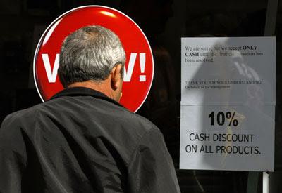 Un hombre lee el cartel en un comercio de Nicosa que avisa que sólo acepta pagos en efectivo.