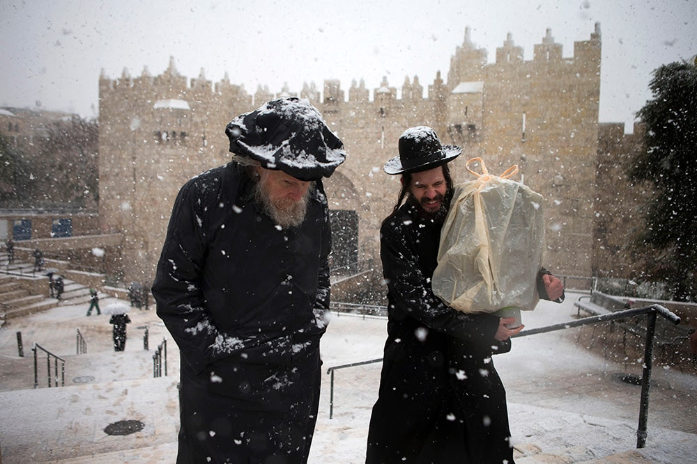 Orthodox jews walk past the Damascus gate in Jerusalem. (Uriel Sinai/Getty Images)
