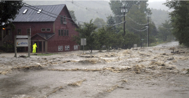A person searches for anyone who may be occupying the building as raging flood waters from Tropical Storm Irene cross Route 100, closing the main road to traffic in Waitsfield, Vt., Sunday, Aug. 28, 2