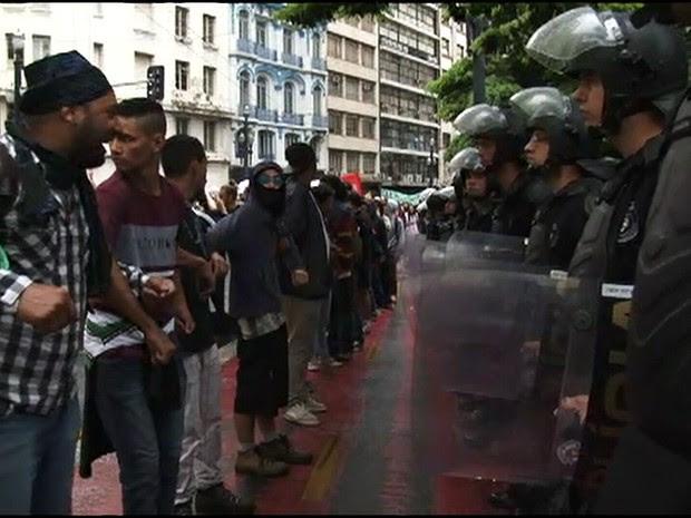 Mascarados encaram PMs durante protesto no Centro (Foto: Reprodução/G1)