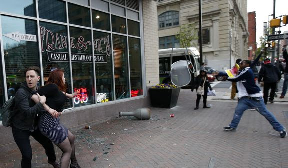 A man, right, throws a chair at a business window as another man tries to restrain a woman attempting to stop the damage, after march to City Hall for Freddie Gray, Saturday, April 25, 2015 in Baltimore. Gray died from spinal injuries about a week after he was arrested and transported in a police van. (AP Photo/Alex Brandon)