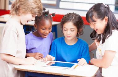 <p>Niños de diversas etnias hablando alrededor de una tableta. / Fotolia</p>