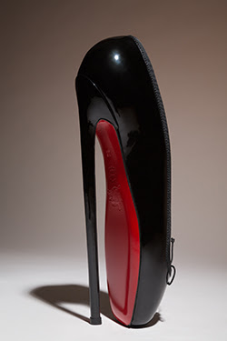 black pointe-style shoes with high heel and signature red sole