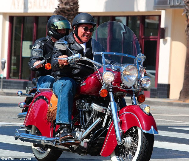 Happy day: Wearing a biker jacket, black helmet and sunglasses, the former California Governor was all smiles as he rode along