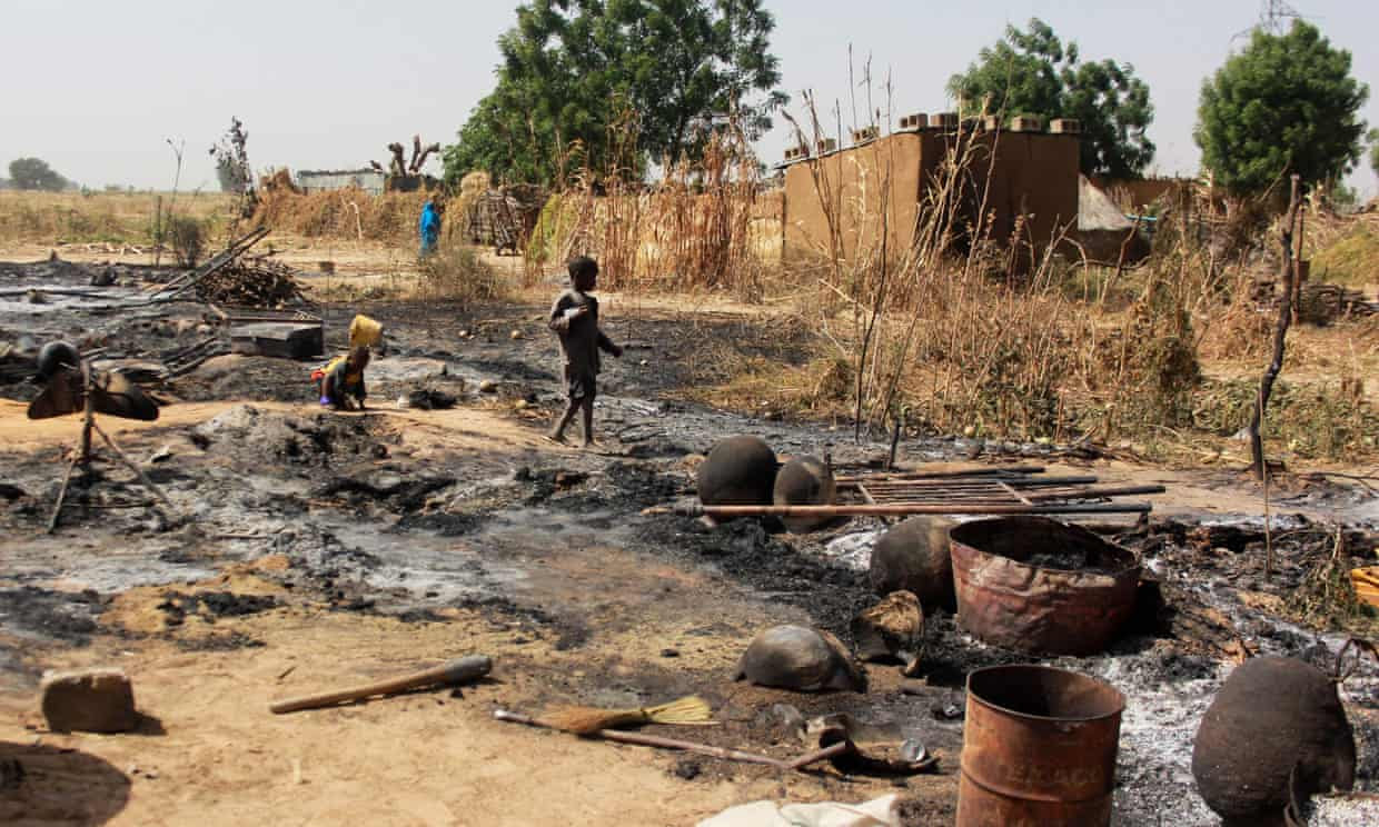 A boy walks past the remains of a village burnt down by Boko Haram on the outskirts of Maiduguri