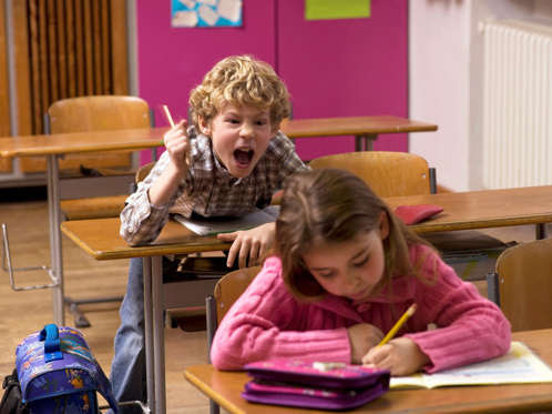 Boy shouting behind girl in class room.