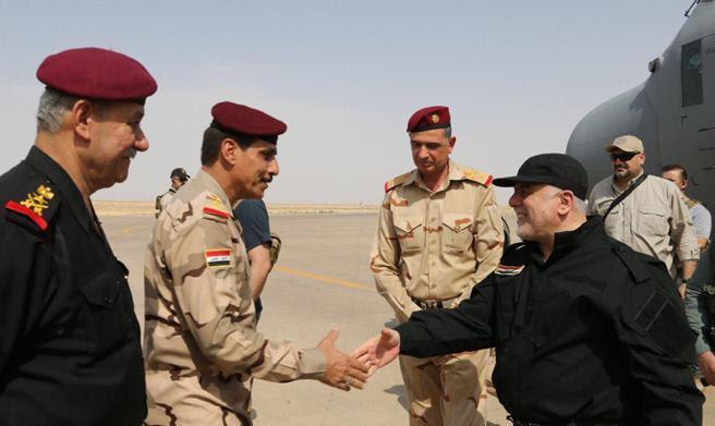El primer ministro iraquí, Haider al-Abadi (derecha), saluda a los oficiales a su llegada a Mosul