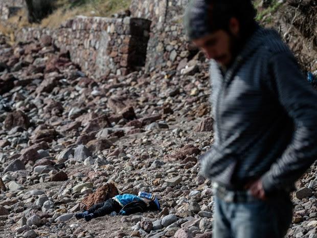 O corpo de uma criança imigrante morta no naufrágio do Mar Egeu é vista na praia de Canakkale em Bademli, na Turquia (Foto: Ozan Kose/AFP)