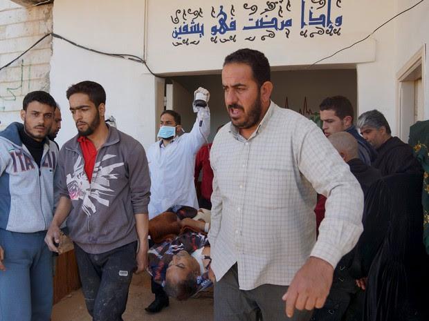 Homens transportam um civil ferido depois de bombardeios nesta sexta-feira na cidade de DAel, na Síria (Foto:  Reuters/Alaa Al-Faqir)