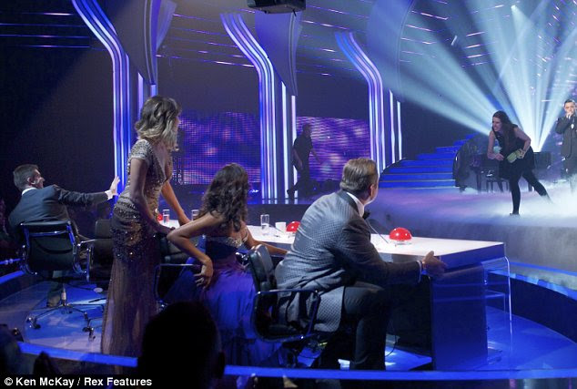 Eggs cellent: Awoman invaded the stage to throw eggs at Simon Cowell as brothers Richard and Adam performed