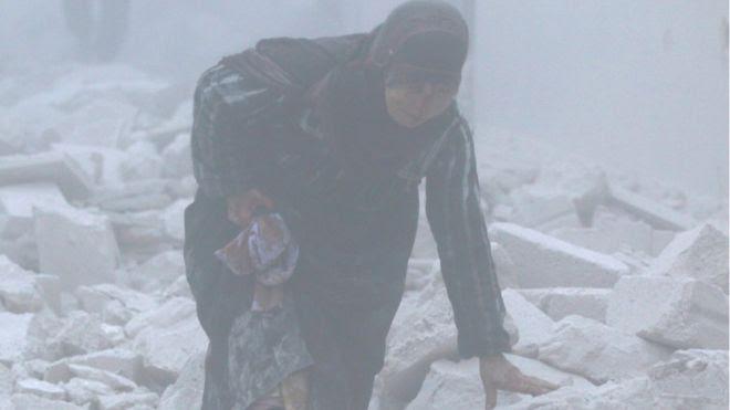 سيدة سورية وسط حطام منزلها الذي هدمه القصف في حلب القديمة