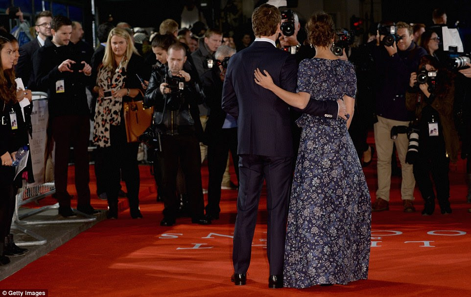 Touchy feely: The couple wrapped a protective arm around one another as they smiled for the cameras on the red carpet