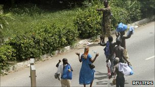 Civilians raise their hands as they walk past a pro-Gbagbo soldier, Abidjan Ivory Coast (April 3, 2011)