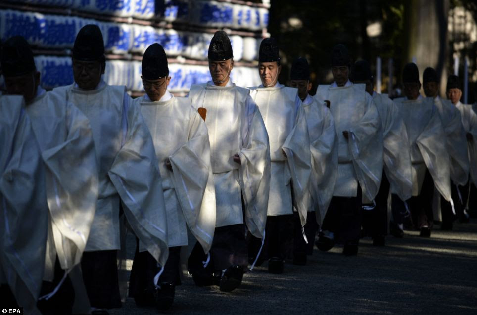 Shinto priests walk toward the main hall to hold a shinto ritual in preparation for the New Year at Meiji Shrine in Tokyo, Japan. It is expected that around three million people will visit the shrine to pray for their health, happiness and property during the first days of 2014