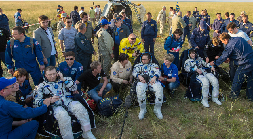 Members of Expedition 42 and 43 sitting outside the Soyuz spacecraft just minutes after landing in Kazakhstan. Credit: NASA/Bill Ingalls