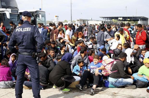 Migrantes aguardam para embarcar em ônibus em Nickelsdorf, na Áustria, nesta segunda-feira (14); cidade fica na fronteira com a Hungria, que foi fechada (Foto: Leonhard Foeger/Reuters)