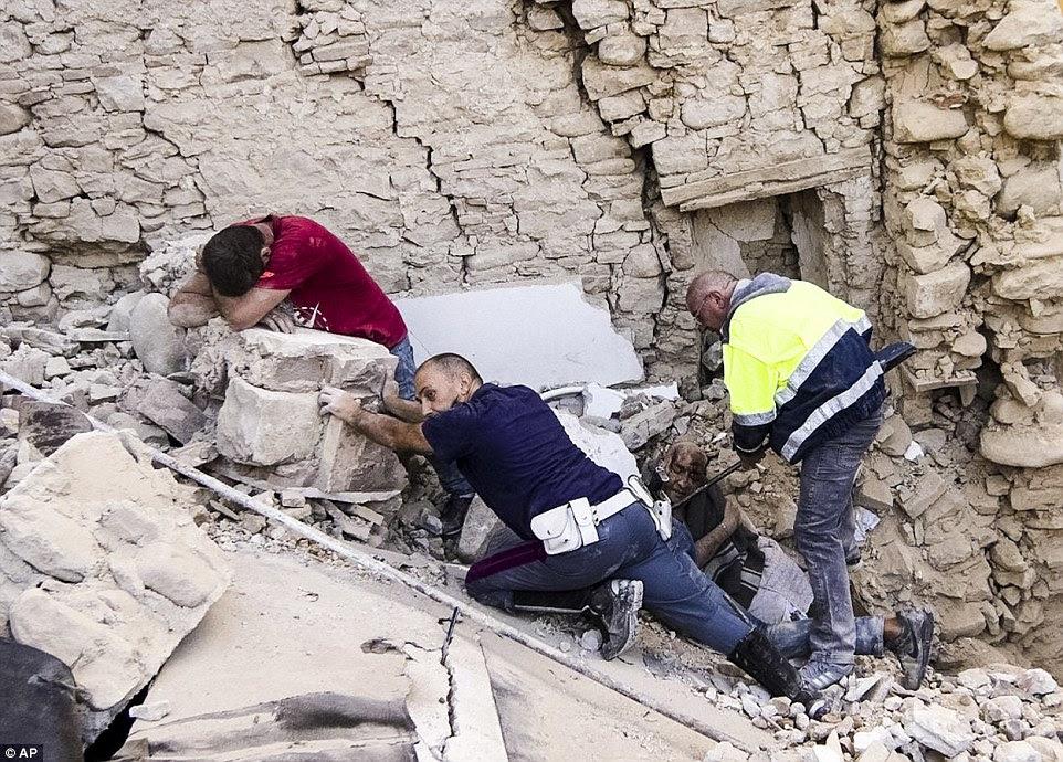Salvo: Um homem chora (à esquerda) como o lesionado local é delicadamente retirados dos escombros, enquanto outro socorrista evita tijolos de deslizar para baixo em cima dele