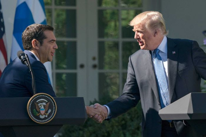 Donald Trump shaking hands with Alexis Tsipras from behind podiums at a press conference at the White House.