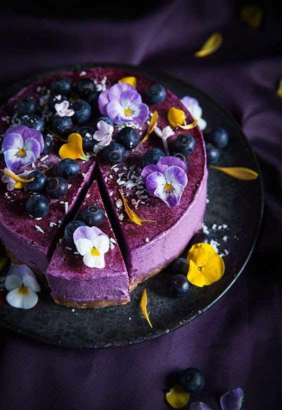 lila Hochzeit Käsekuchen mit essbaren Blüten und Blaubeeren