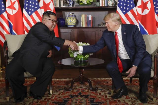 Kim Jong-un serre la main de Donald Trump... (PHOTO EVAN VUCCI, ARCHIVES ASSOCIATED PRESS)