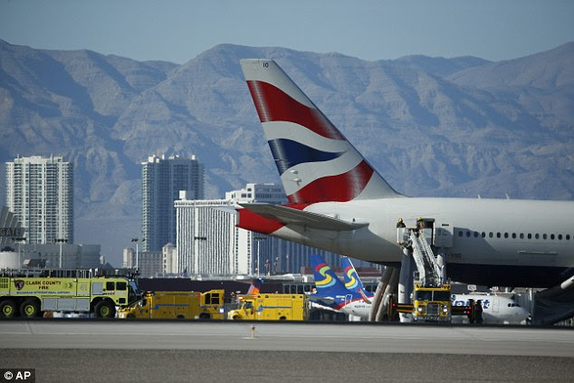 Firefighters stand by a plane that caught fire at McCarren International Airport