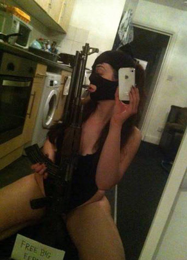 Caitlin Adams posing with an AK-47