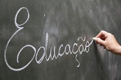 Foto de um quadro negro, onde se lê a palavra 'Educação' escrita a giz pela mão de uma pessoa.