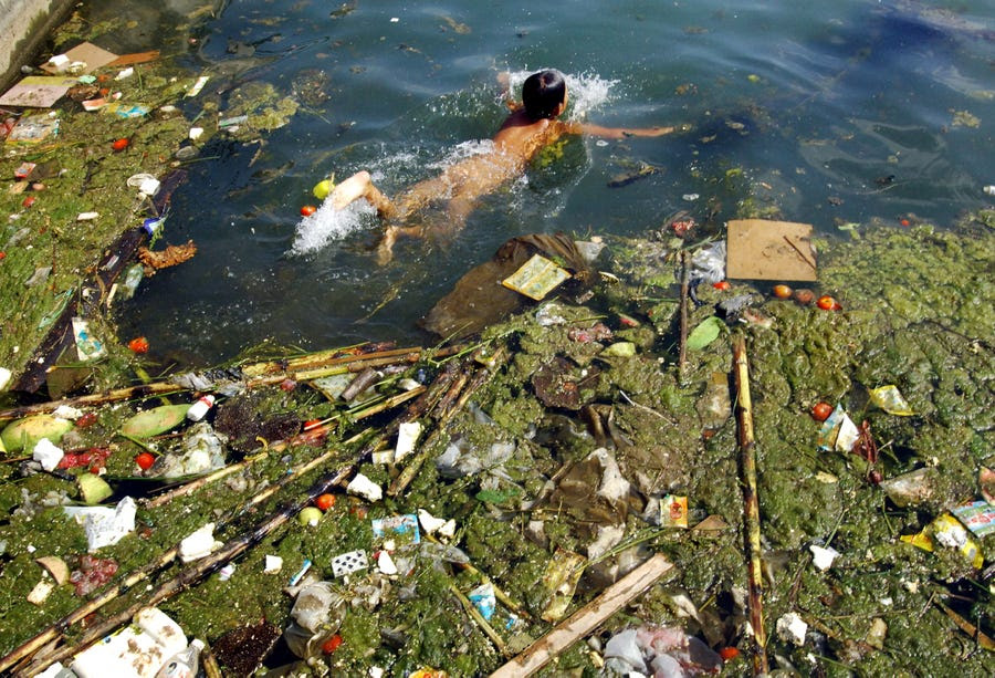 A child swims in a polluted reservoir, southwest of China's Guizhou province, in September 2006.